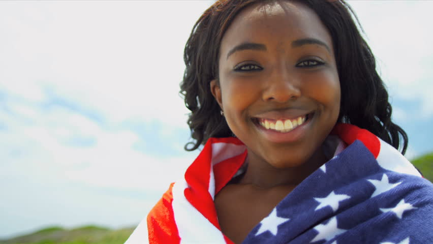 African American Beach Girl wrapped in American Flag. Slow motion.