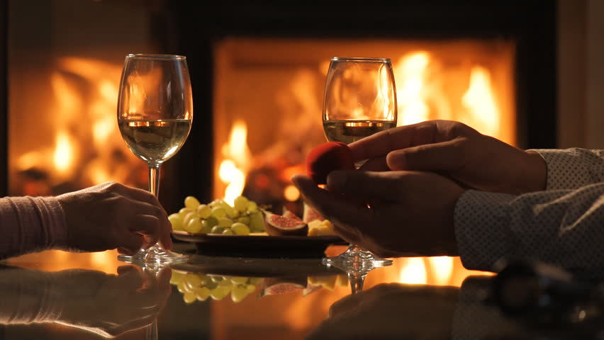 Happy Young Couple Sitting Near Fireplace And Drinking