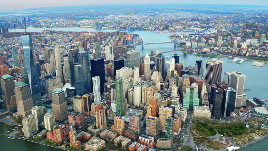 Aerial view of the Financial District. Famous Skyscrapers in Lower Manhattan. Brooklyn and Manhattan Bridge in the background. New York City, United States. Shot from a helicopter.