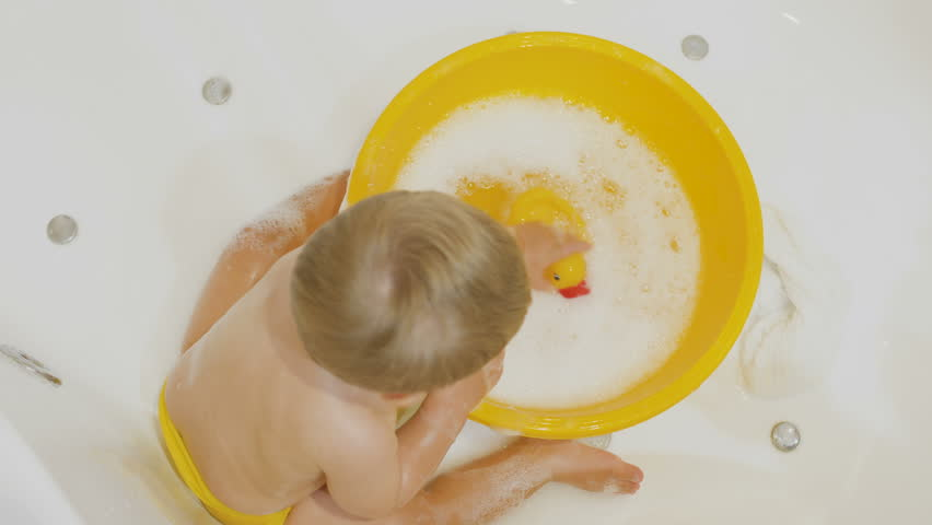 Little boy plays with rubber duck in the bath
