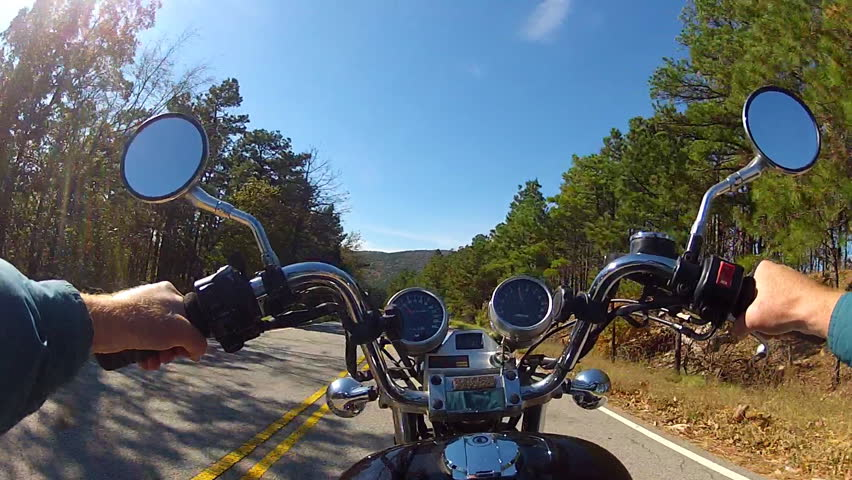 A wide angle point of view shot from a chest mounted camera on a motorcyclist