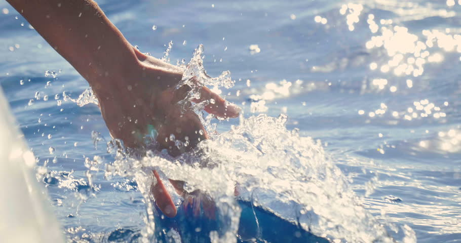 Slow motion of a female hand is touching a clear transparent water and enjoys the day at the sea alongside the waves of the boat. Concept of happiness, boat life and holidays in exotic places #31131262