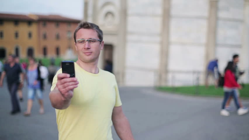 Man taking photo with cellphone by Leaning Tower of Pisa