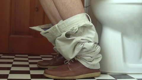 Businessman's feet as he sits on a toilet in the bathroom
