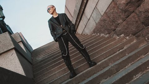 Androgynous queer bald caucasian girl in rock outfit leather jacket chains on pants and sunglasses stomp foot in rhythm outside on staircase