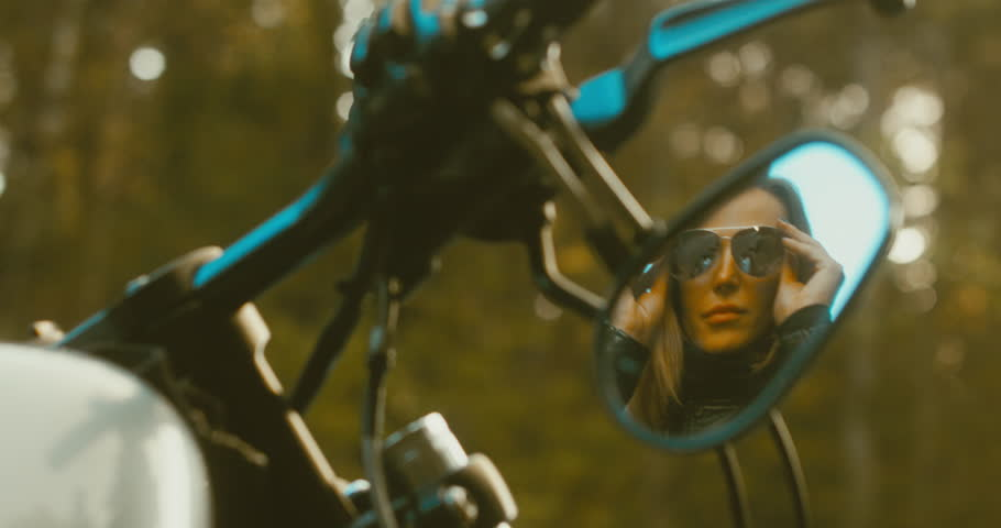 Reflection in rear view mirror, beautiful adult female biker putting on sunglasses before the ride. 4K UHD RAW edited footage