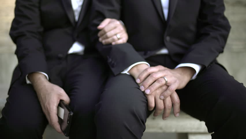Great slow motion of a couple of a homosexual gay couple of men in black suit with wedding rings and a smartphone in the hand.