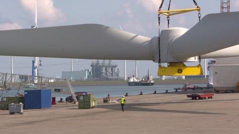 EEMSHAVEN, THE NETHERLANDS - SEPTEMBER 2017: hoisting wind turbine rotor blades on board an offshore construction vessel.