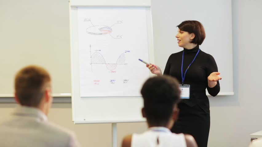 Business, education and strategy concept - businesswoman showing charts on whiteboard to group of people at conference presentation | Shutterstock HD Video #31241812
