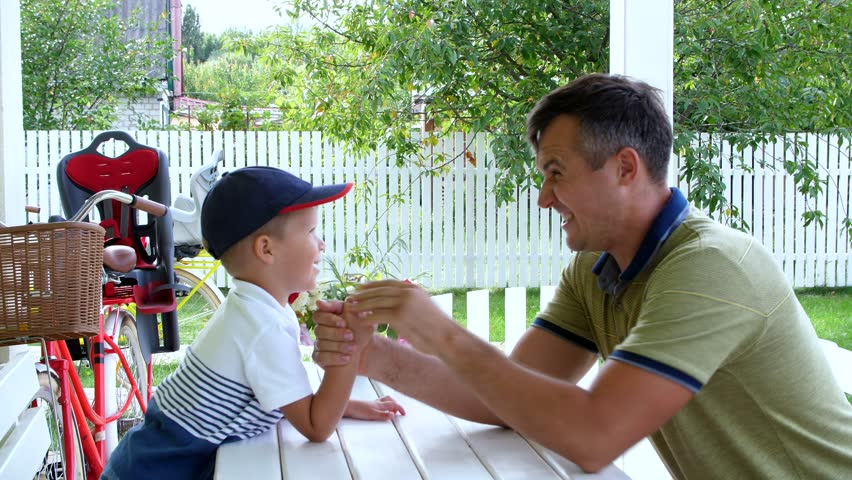 Dad and his four-year-old son play together in armwrestling, they are having fun. In the summer, in the garden.