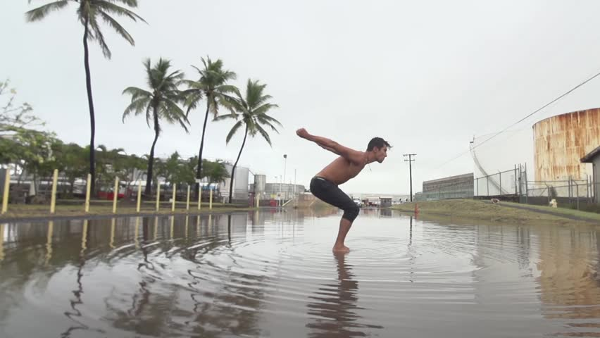 Slow motion backflip in muddy reflective puddle