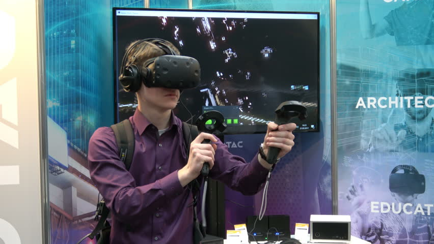 Hannover, Germany - March, 2017: 4K video footage of man playing video game in virtual reality headset and handheld controller developed by HTC Vive on exhibition Cebit 2017 in Hannover Messe, Germany | Shutterstock HD Video #31249972