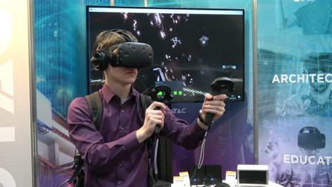 Hannover, Germany - March, 2017: 4K video footage of man playing video game in virtual reality headset and handheld controller developed by HTC Vive on exhibition Cebit 2017 in Hannover Messe, Germany