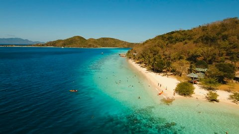 Aerial view of tropical beach on the island Banana, Philippines. Beautiful tropical island with sand beach, palm trees. Tropical landscape: beach with palm trees. Seascape: Ocean, sky, sea. 4K video