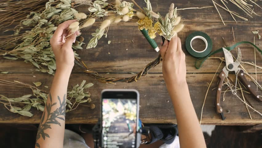 Top viwe of smart phone attached to tripod and blogger influencer streaming video in internet online to give lessons on floral design and wreath creation. Many followers hit like for inspiration