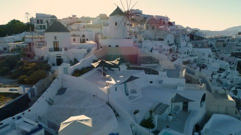 Flying above white houses and famous old castle ruins on Santorini Island, Greece. Village of Oia. Morning sunshine rays.