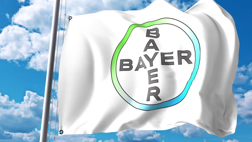 Waving flag with Bayer AG logo against clouds and sky. 4K editorial animation