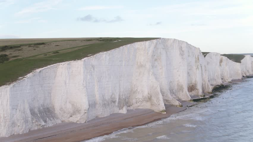 Dramatic aerial reveal at speed of white chalk cliffs of Beachy Head Beachy Head and shore line in the UK