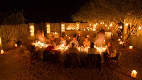 Sabi Sands, Mpumalanga, South Africa - 03/31/2017 A joyful evening as the lodge guests enjoy a boma dinner around the campfire and Acacia thotn trees at Londolozi.