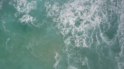 Vertical Aerial view of drone flight above turquoise ocean water, wave surf in slow motion, with scenic textures and patterns as background.