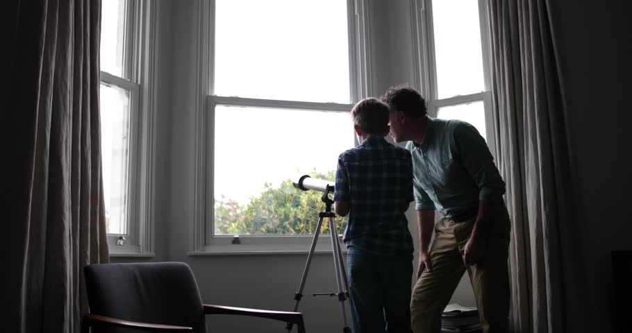 Father and Son looking at view with a telescope