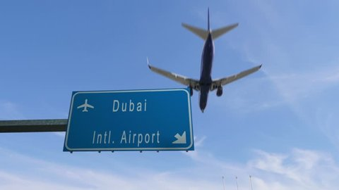 dubai airport sign airplane passing overhead