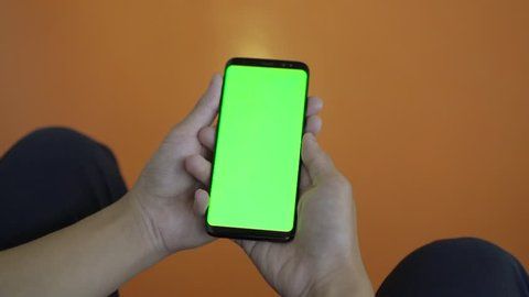 Boy sitting and using mobile smart phone with green screen in library. Close up of thumb scrolling up through touch screen display