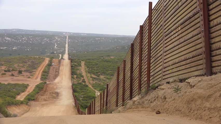 CIRCA 2010s - U.S.-Mexico border - Border patrol vehicle sits in the distance near the US Mexico border with an American flag flying background.