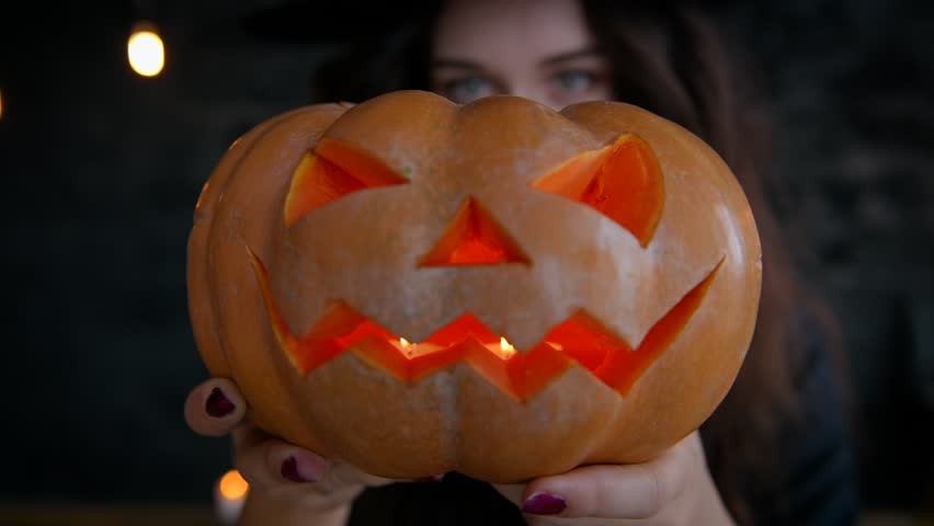 Girl witch on Halloween on a ,holding pumpkin with a burning candle and casting a spell. Jack-O-lantern.
