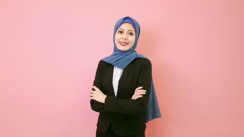 Professional confident muslim business woman hands crossed looking at camera and wearing suit clothing standing in pink background.