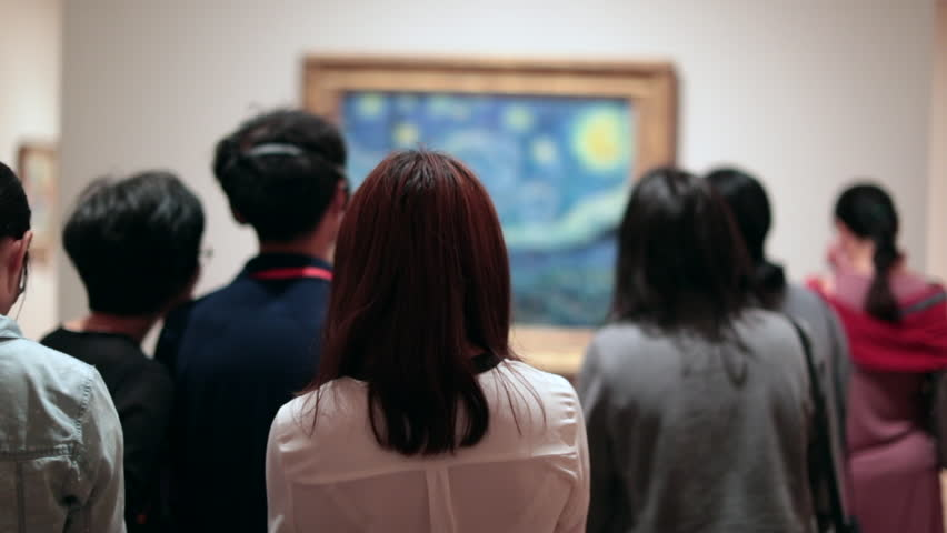 People looking at a work of art. Public starring at a painting at a museum. Group of people contemplating a work of art