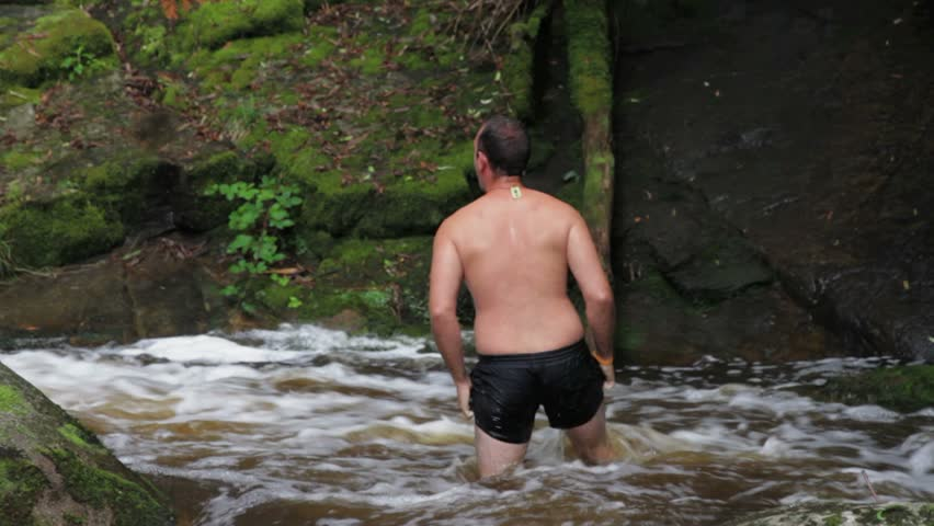 Male goes for a swim in raging river between rocks in Rainforest, Noojee, Victoria, Australia #3141892