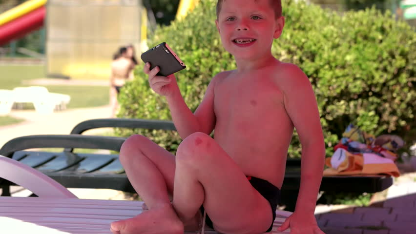 Young Boy With Smartphone or Tablet Sitting in neatr the Pool on a chair. Play, Game, Mobile Applications, Children | Shutterstock HD Video #31437232