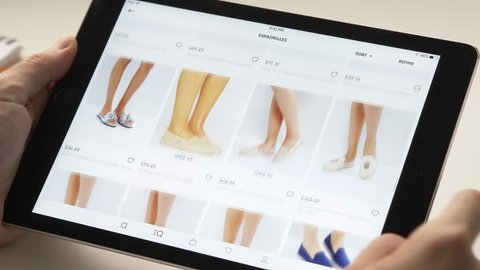 Shopping online on a tablet device looking to buy some woman's footwear. Browsing different choices.