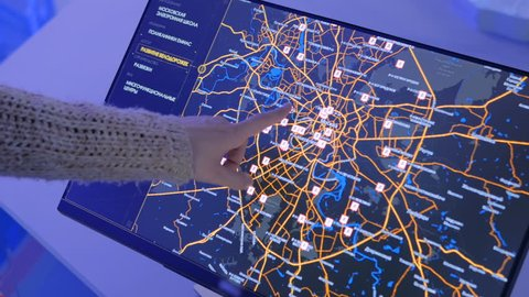 MOSCOW, RUSSIA - SEPTEMBER 10, 2017: Smart City Exhibition. Woman using interactive touchscreen display with virtual map of Moscow at modern technology show