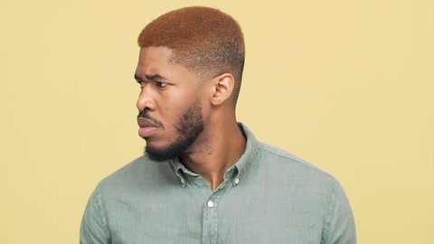 picture of dark-skinned guy with stylish haircut in blue skirt looking angrily from side to side then showing on camera with index finger, over yellow background slow motion closeup. Concept of