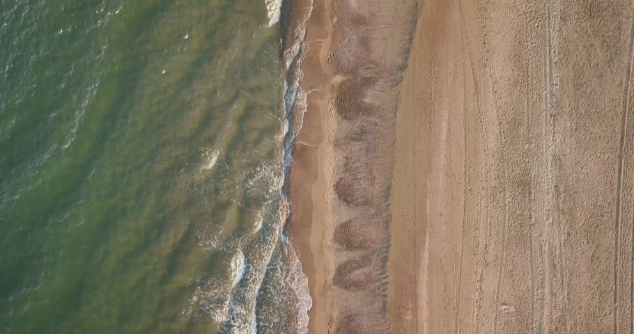 Aerial view of waves crashing on the beach while a men is running at sunset, Video Shot in Sabaudia, a beautiful beach on the west coast of central Italy.