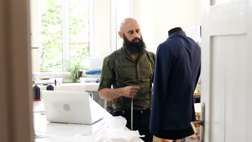 The tailor is measured by the lapel of the jacket on the mannequin | Shutterstock HD Video #31469980