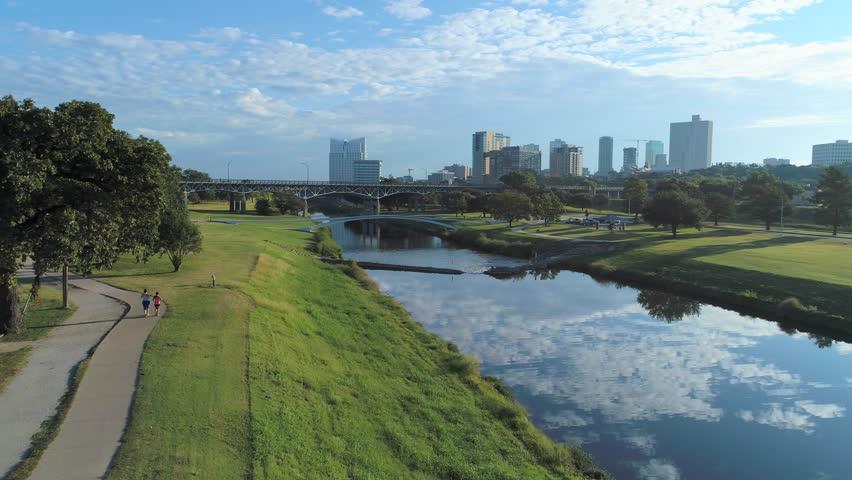Aerial Fort Worth's Trinity Park w/ skyline, river reflection trails- cyclists