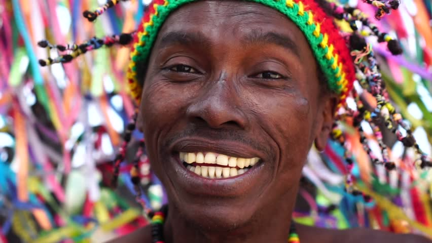 Brazilian african smiling and background is a colorful religious brazilian ribbons in Salvador, Bahia, Brazil