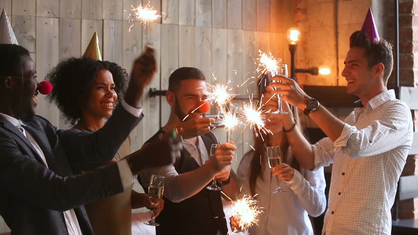 Multiracial young people wearing funny hats holding sparklers clinking glasses with champagne, happy african american and caucasian friends celebrating xmas, new year or birthday party indoors, cheers