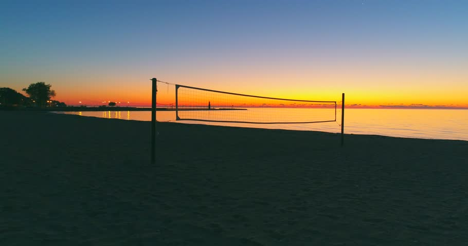 Flying past volleyball net on unoccupied Autumn beach, out over lake Michigan in colorful predawn twilight.