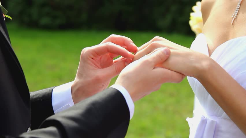 Closeup of bride and groom exchanging wedding rings over green nature background | Shutterstock HD Video #3153232