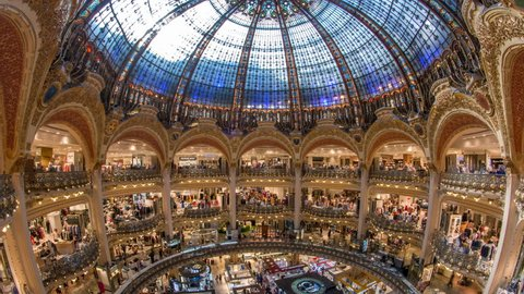PARIS, FRANCE - CIRCA JULY 2017: Galeries Lafayette interior from top timelapse in Paris. People do shoping at department store. The architect Georges Chedanne designed the store where a Art Nouveau