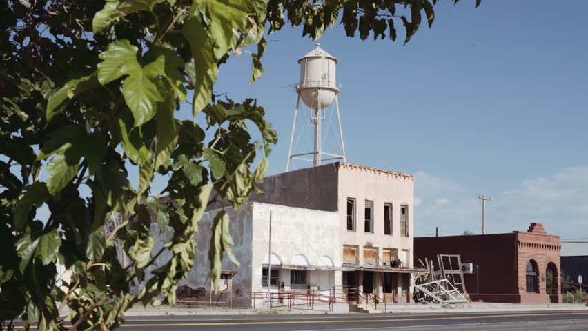 Abandoned Ghost Town with Water Tower. shot moves from a tree and reveals an abandoned ghost town main road with a water tower