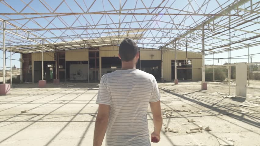 Tracking shot of a man walking in an abandoned factory | Shutterstock HD Video #31550896