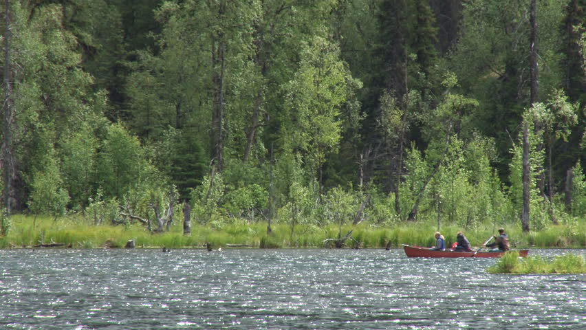 TERN LAKE, AK - CIRCA 2011: Three people in a red canoe on Tern Lake in Alaska. The white bird that flies overhead in the middle of the clip is a tern.