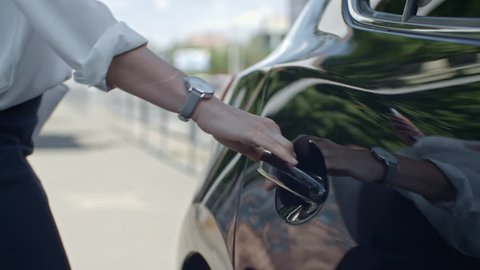 Closeup of hand of businesswoman opening door and getting into car on street