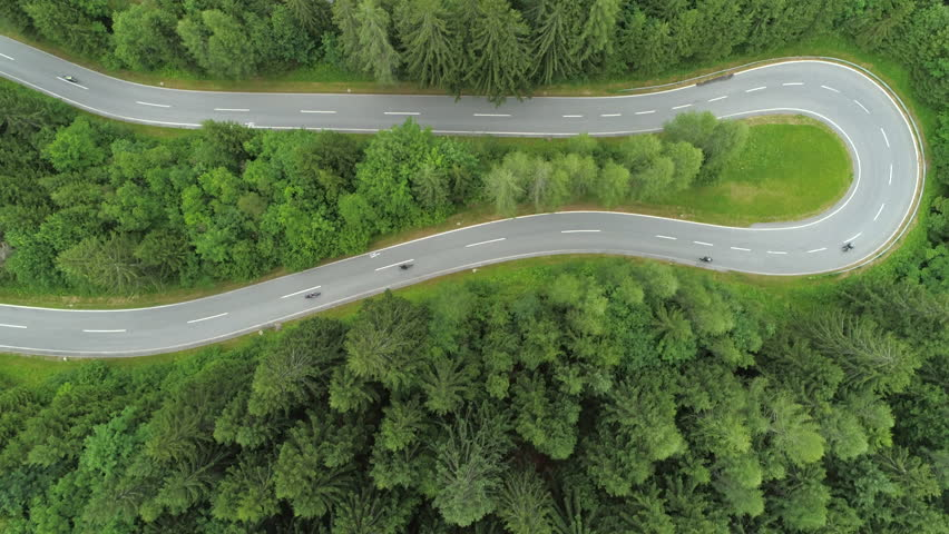 AERIAL, TOP DOWN: Bikers on motorcycles speeding through sharp turns on winding zig zag serpentine road. White car driving on winding undulating mountain highway in beautiful lush green spruce forest