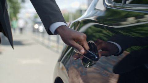 Closeup of hand of African businessman opening door and getting into car on street
